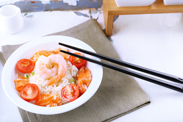 Boiled rice and shrimps, salmon and tomatoes in bowl,