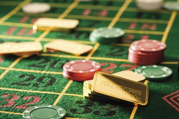 Spielende Chips und Goldbarren auf Roulette-Tisch