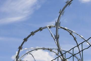 Razor Barbed wire against a blue sky, closeup