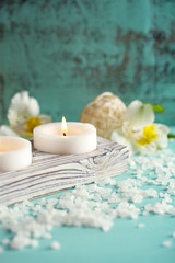 Candles, bottles sea salt and spa stones on wooden background