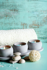 Candles, towel, sea salt and spa stones on wooden background