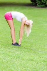Junge Frau macht Dehnübung im Park
