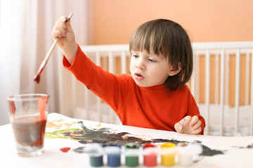 lovely little 2 years boy painting at home