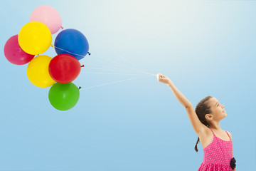 Little girl with balloons on sky background