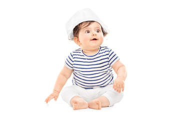 Cute baby girl in sailor outfit sitting on the floor