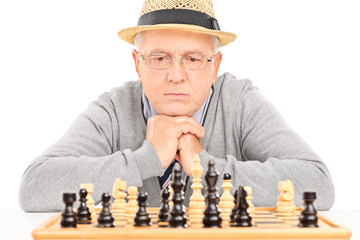 Senior contemplating his next move in game of chess