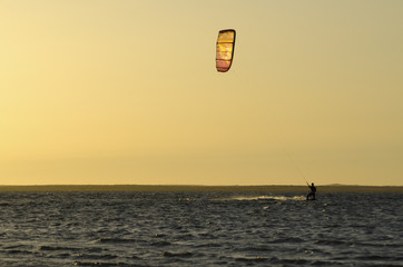 Kitesurfer riding at the sunset