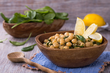 Spiced chickpeas with spinach in a wooden bowl