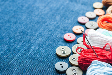 Blue jeans background with buttons and threads.
