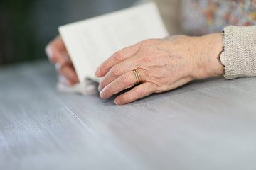 Closeup of elderly woman's hands with book