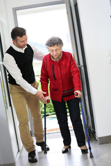 Man helping elderly woman with crutches