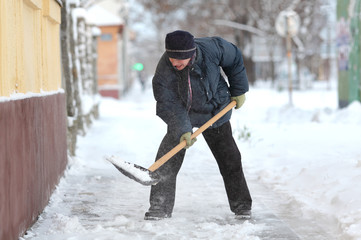 Caucasian woman cleaning snow from sidewalk with shovel