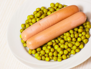 sausage with green peas on a white plate