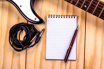 open notebook with electric guitar on wooden background