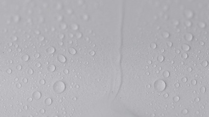 Water drips and flows down on a white surface. 4K UHD video.
