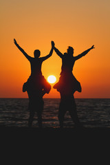 silhouette teens sitting on shoulders of friends in sunset