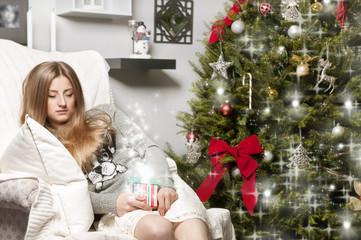 Girl dreaming near christmas tree