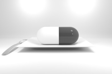 large grey pill on white plate and silver spoon