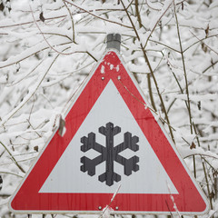 winter warning sign shows danger of ice and snow at street
