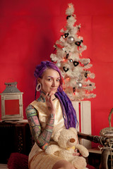 Christmas photo of a girl with purple dreadlocks and tattoos