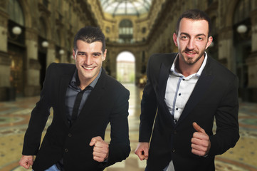 Two young businessmen run in city center
