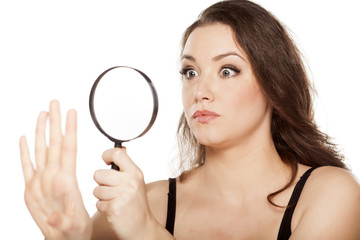 astonished woman looking at her nails with a magnifying glass