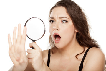 shocked young woman looking at her nails with a magnifying glass