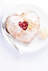 Heart shaped cherry pie with vanilla ice cream on white