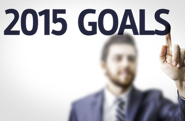 Business man pointing to transparent board with text: 2015 Goals