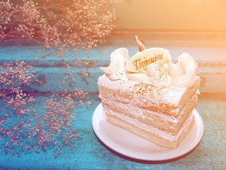 A piece of tiramisu cake in warm light on blue wooden background
