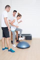 Zwei Trainer helfen älterer Frau mit Fitnessübung