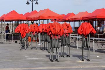 Aufbau von Marktständen mit rotem Sonnenschutz