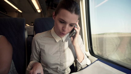 Businesswoman talking on cellphone and reading documents on a tr