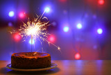 Tasty cake with sparkler on shiny background
