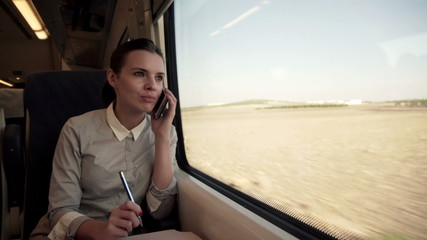 Young businesswoman talking on cellphone on a train