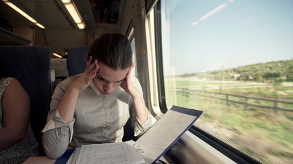 Overwhelmed, sad businesswoman with documents sitting on a train