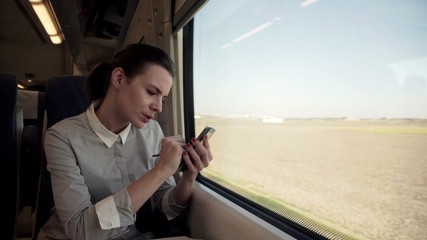 Businesswoman writing notes on smartphone sitting on a train