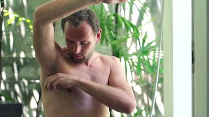 Man applying antiperspirant after shower on his armpit