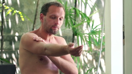 Man applying moisturizing cream on his arm in luxury bathroom