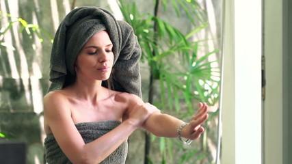Pretty woman applying lotion moisturizer on her arm in bathroom