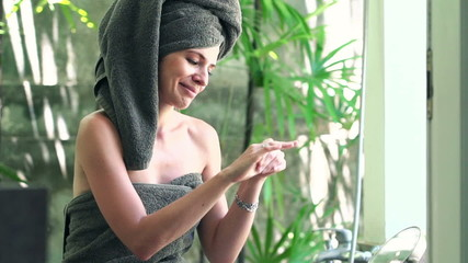 Pretty woman applying lotion moisturizer on her hands