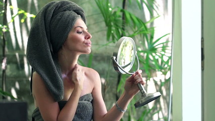 Woman checking her face in the mirror in bathroom
