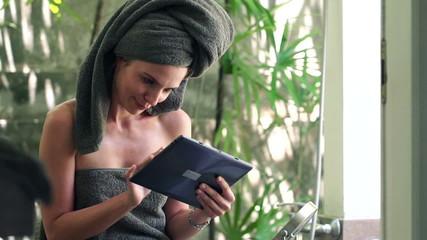 Young beautiful woman with tablet computer in bathroom