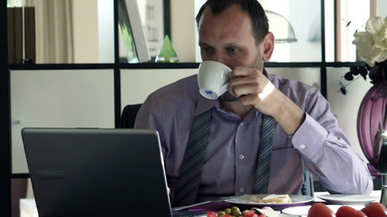 businessman working with laptop during breakfast