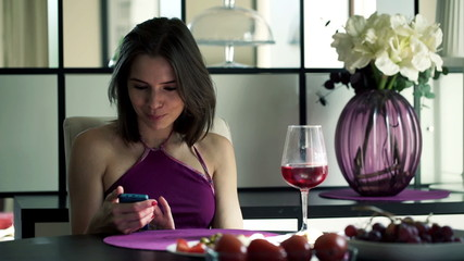 Young woman with smartphone and wine by the table