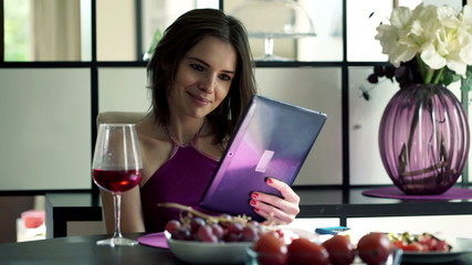 Young woman with tablet computer sitting by the table at home