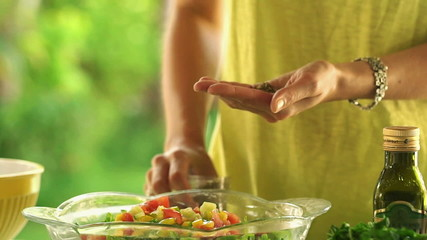 Woman hands adding seasoning to salad in kitchen at home, slow m