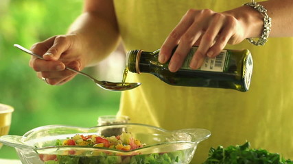 Pouring olive oil on fresh salad in bowl,