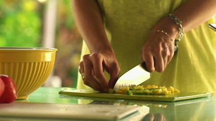 Woman hands slicing and putting pepper into bowl in kitchen