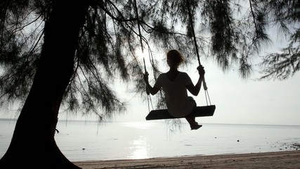 Girl on a Swing on a Beach Looking at the Sea. Slow Motion.